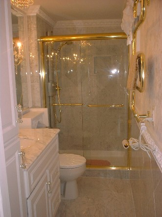 Carra Italian marble covers the walls and floor  Ornate trim work  marble sink  and towel warmer finish this elegant bathroom. Booth Construction  Inc  Bathroom Remodeling